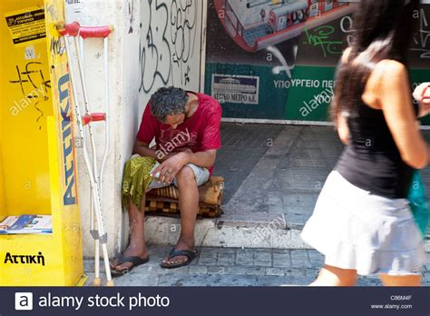 People walk past a homeless man on the street in